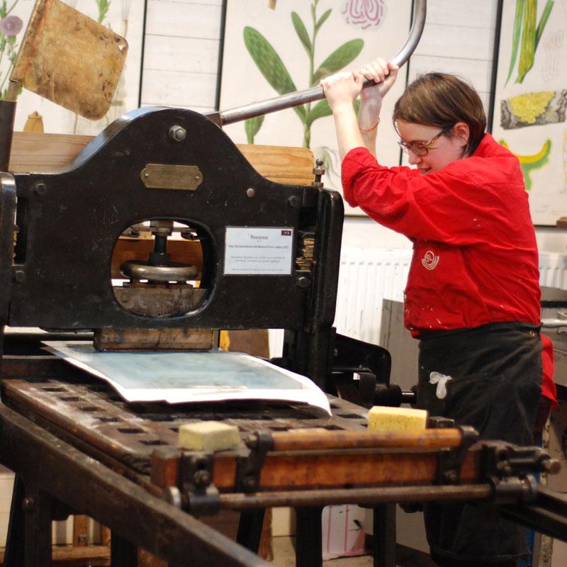 Papper läggs på stenen och körs genom tryckpressen