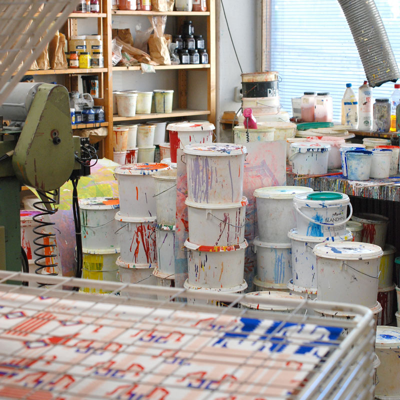 Drying rack for newly printed sheets of paper and a view of the workshops color stock.