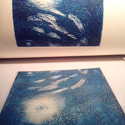 Close-up of the printing process: The paper (above) and the plate (below) during the printing of the first color of two.